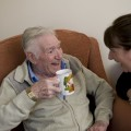 Elderly man with Tea speaking with Staff member