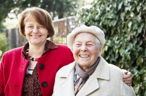 Elderly woman laughing with a friend, Friends of the Elderly befriending services