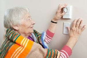 An older woman saving energy by dressing warm and adjusting her thermostat.