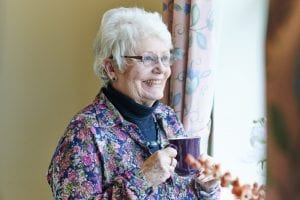An older woman smiling and holding a mug of tea