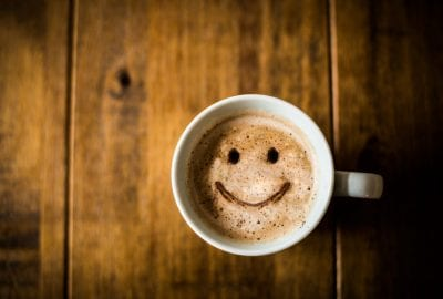 A cup of coffee with a smiley face on it