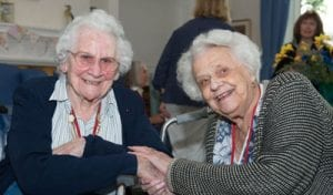 Two residents at Malvern holding hands