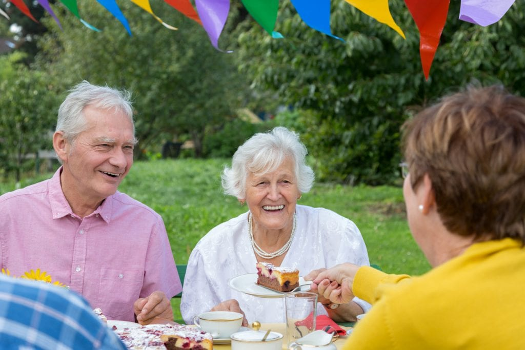 A group of older people sitting at the garden table enjoying a Care Home Open day event