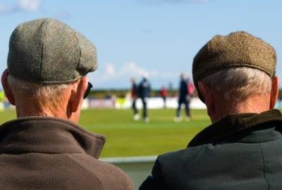 Two older men watching a football match