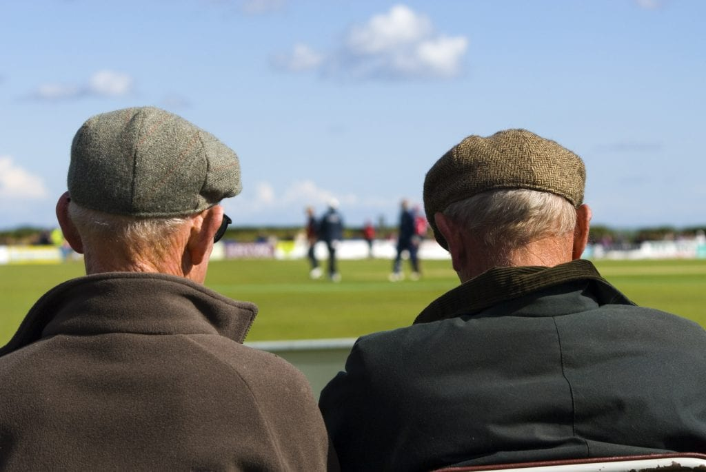 Two older men watching a football match