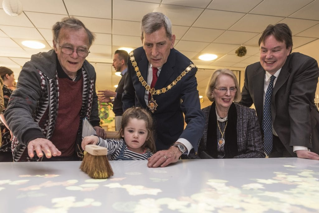 Cllr Ian Johnson, the Mayor of Woking, Cllr Graham Cundy, Mayoress Sarah Cundy and Jonathan Lord MP with a young guest at the Tovertafel launch party