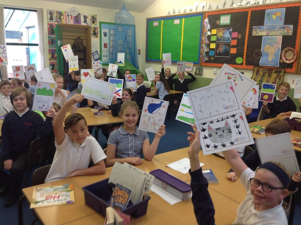 Students from Northleigh School hold up their picture postcards