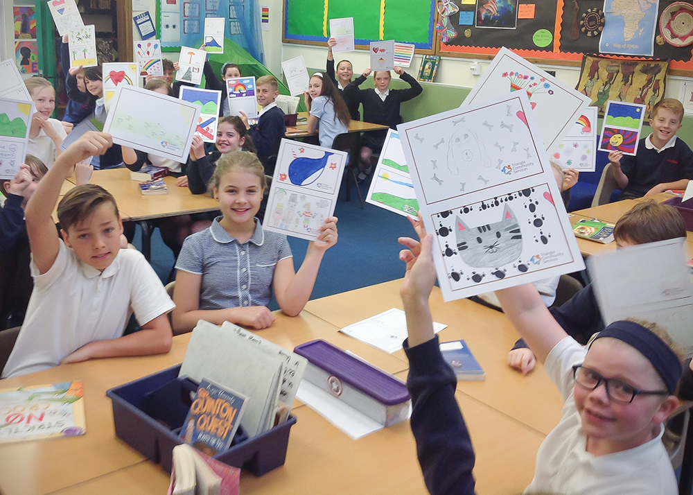 Children from Northleigh School hold up their picture postcards