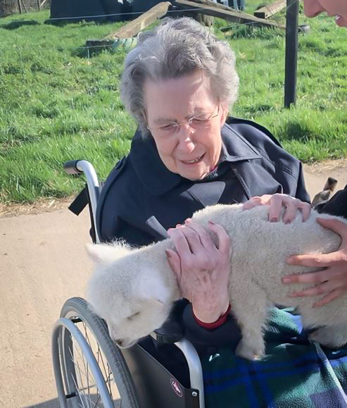 Resident from our Essex care home holding a lamb