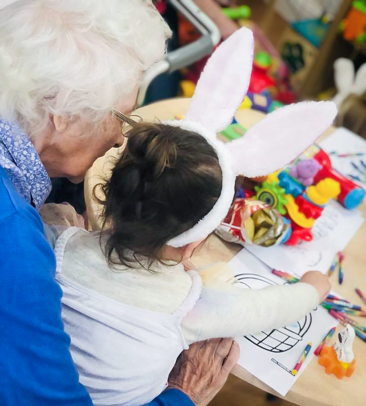 Care home resident and little girl enjoying Easter crafts