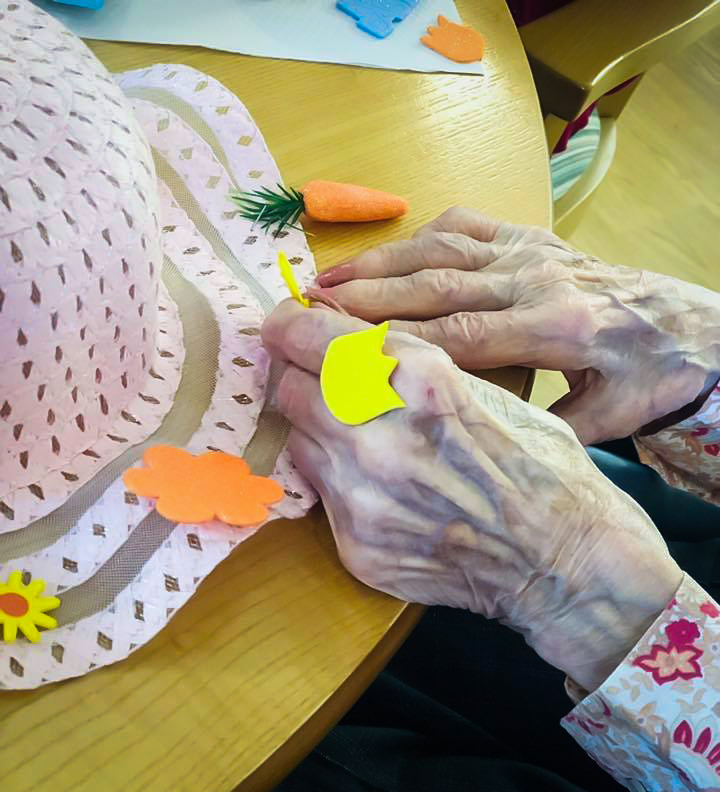 Resident making an Easter bonnet