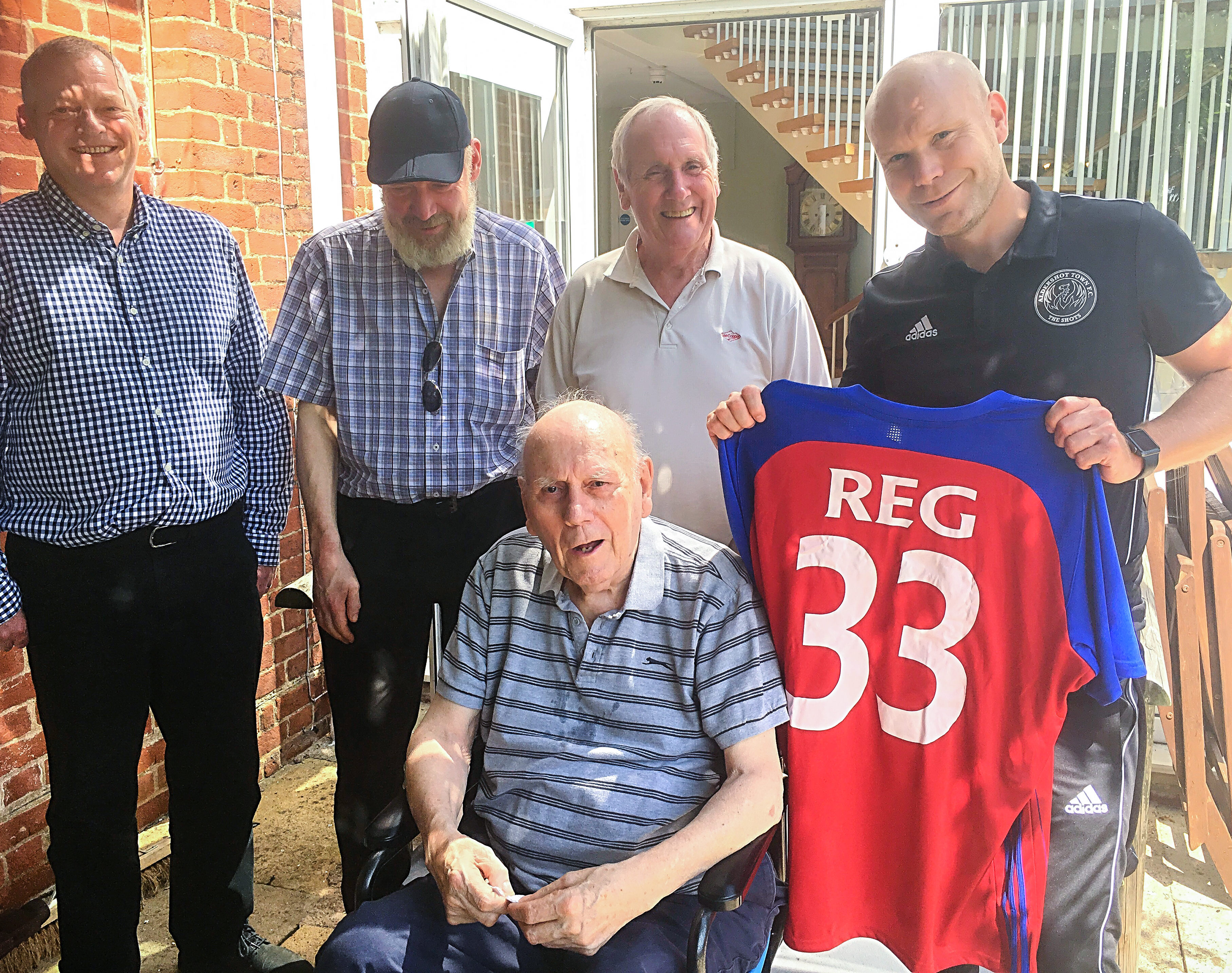Reg Cuff, Aldershot Town Football Club manager Danny Searle and Reg's family stood together with Reg's new shirt