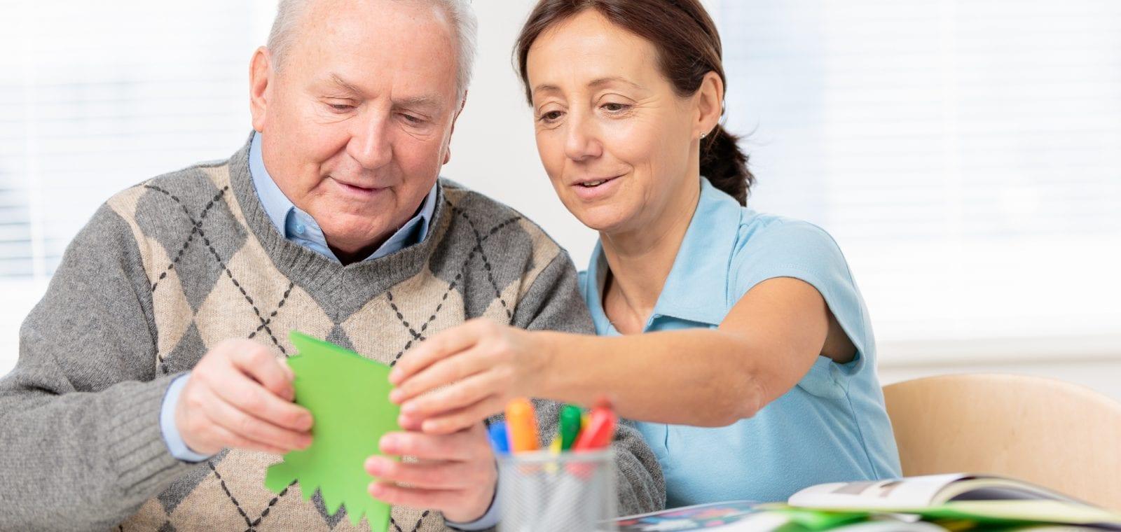 Senior man cutting paper with scissors