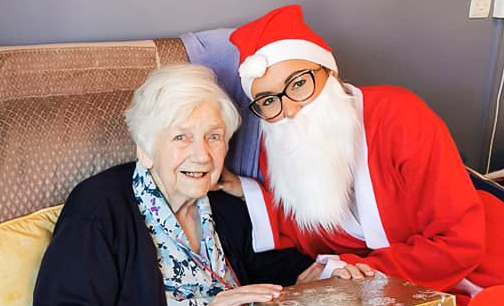 Ewelina dressed as santa visiting a resident at Bernard Sunley care home