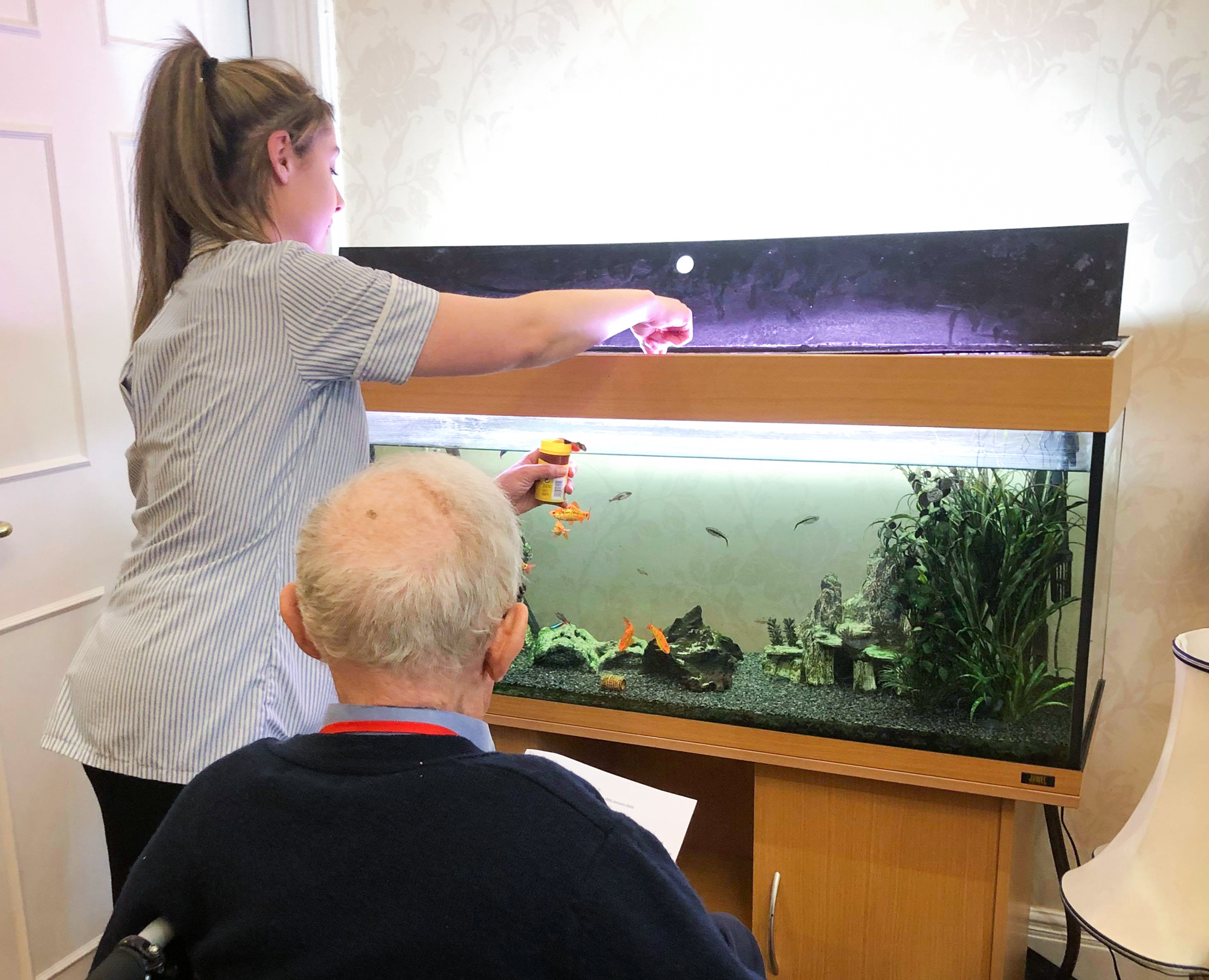 Staff and resident feeding the fish