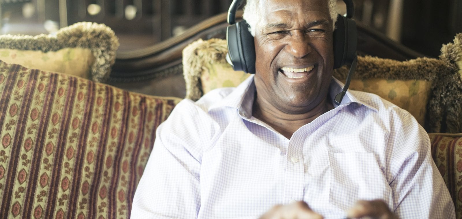 Senior Black Man Playing Video Games with Headphones