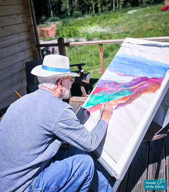 Resident at Orford House, painting on a canvas