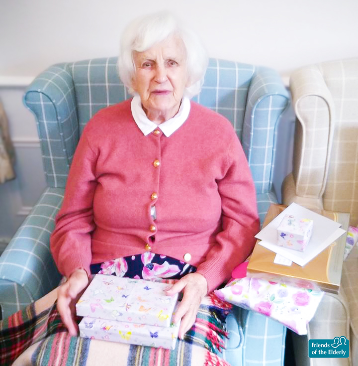 Joan on her birthday with presents on her lap.