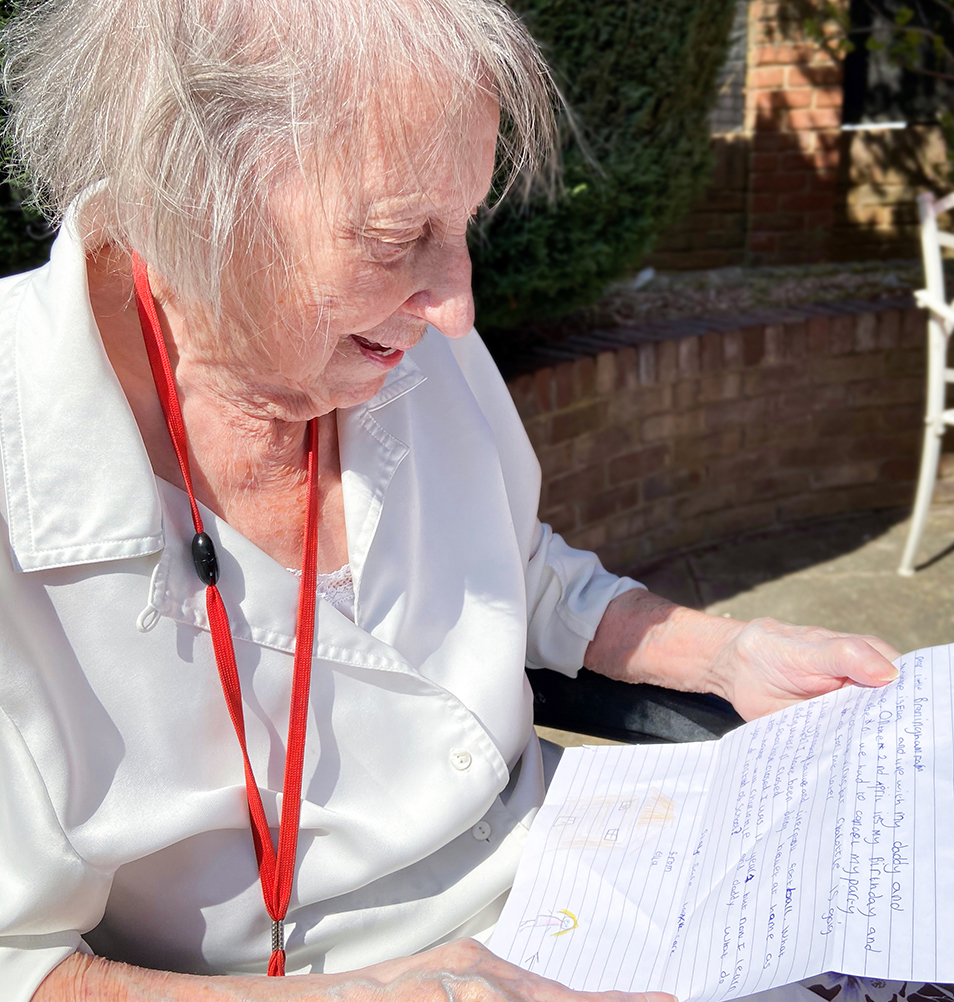 Madge reading a letter of friendship sent by Ella
