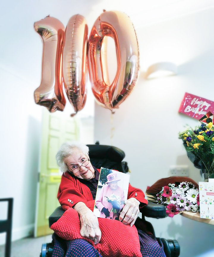 Moyra celebrating her 100th Birthday with balloons, presents and a card from The Queen.