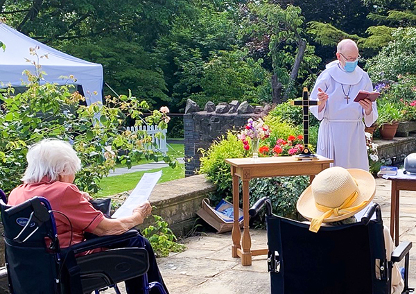 A priest stood in the garden with residents at a safe distance during the church service