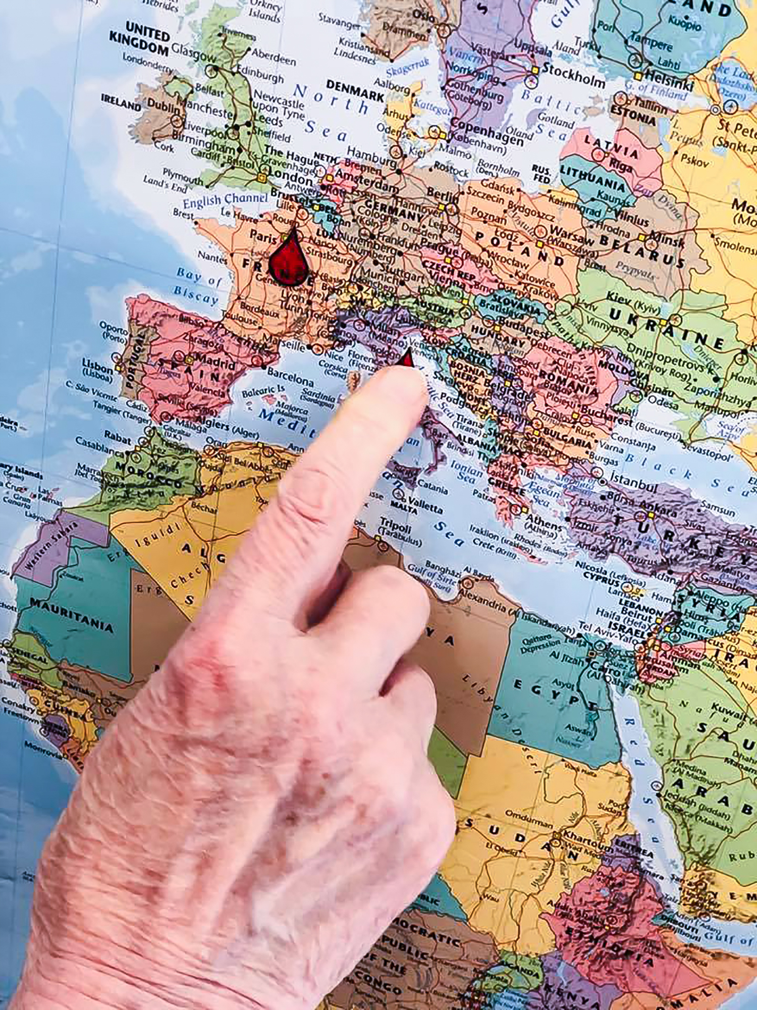 A resident's hand pointing to a world map