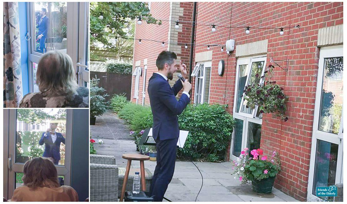 Performer Dan Brewerton sings outside as residents watch from the window inside