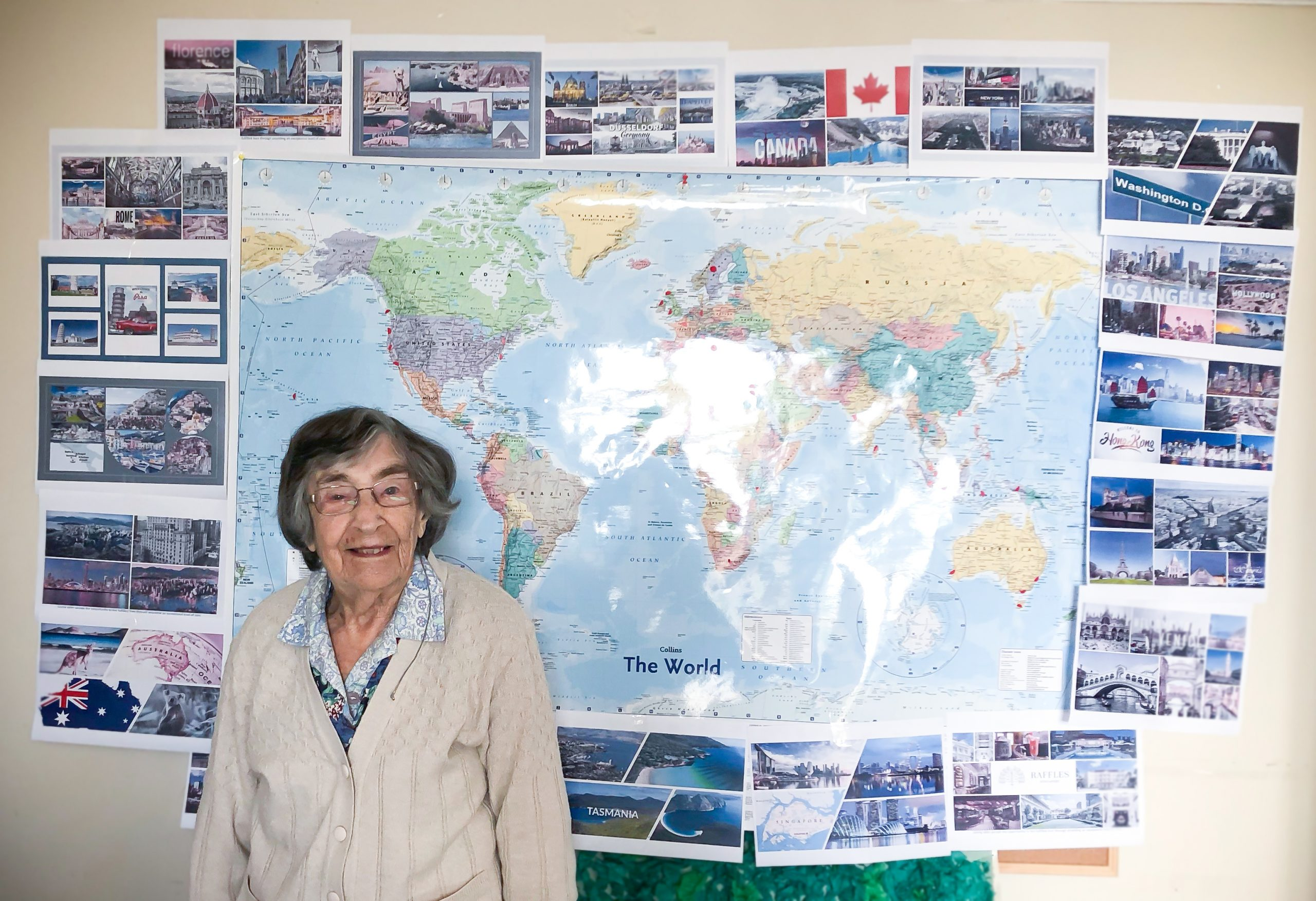 Evelyn standing in front of a world map and images of places she and John visited