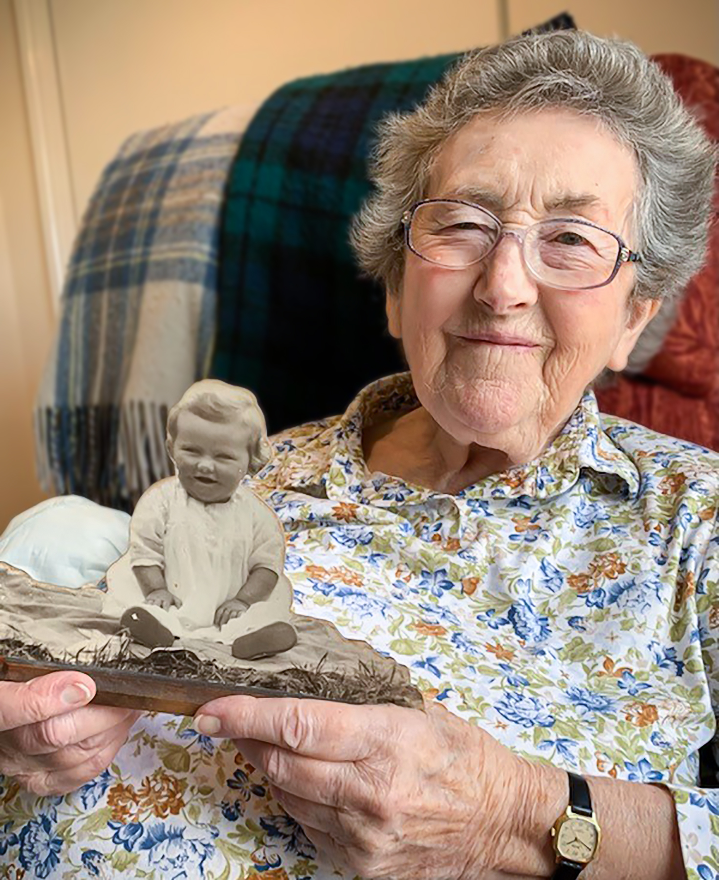 A Malvern care home resident holding a picture of herself when she was young and smiling at the camera