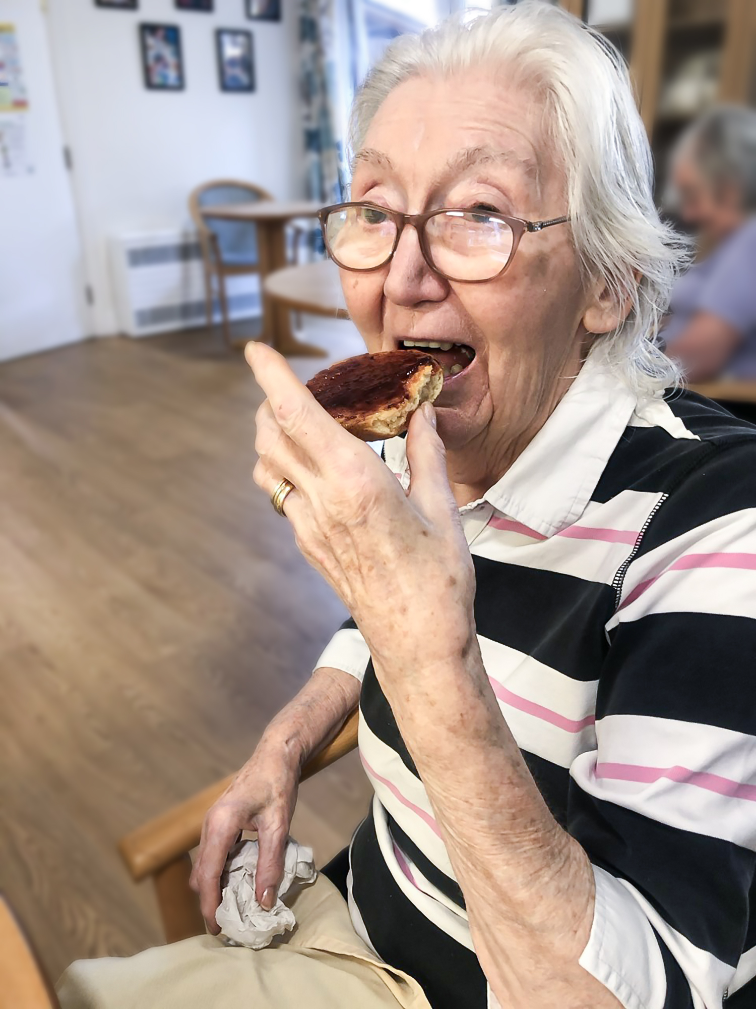 A Bernard Sunley care home resident eating a freshly made scone