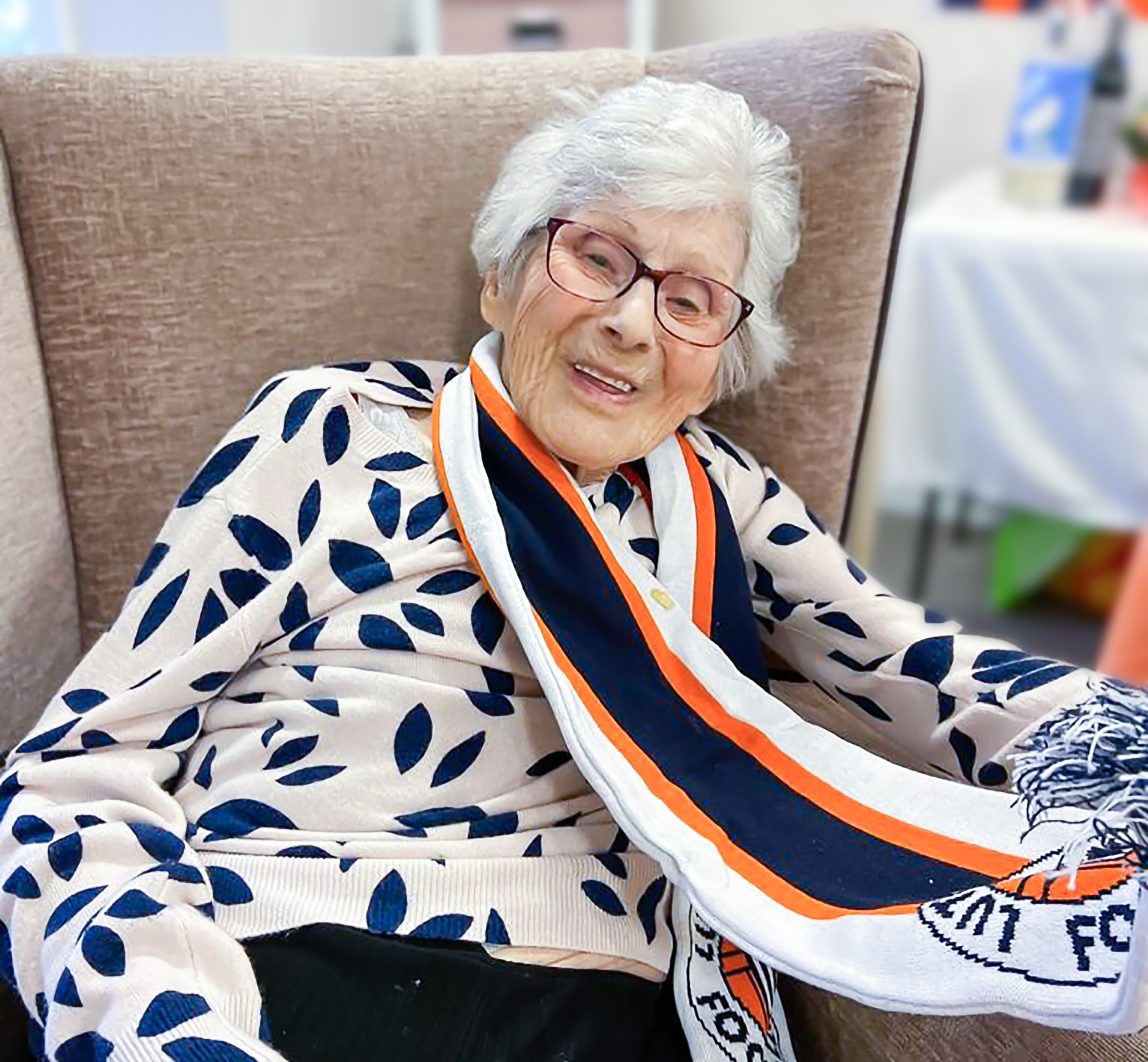 Little Bramingham Farm care home resident smiling and wearing her Hatter's scarf