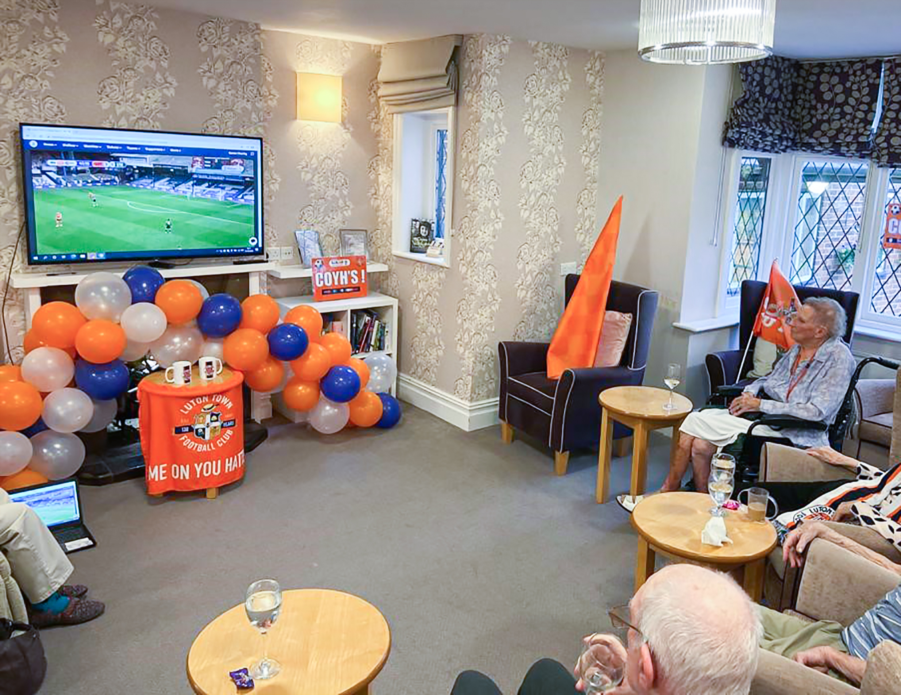 Care home residents watching the football match on TV in the lounge
