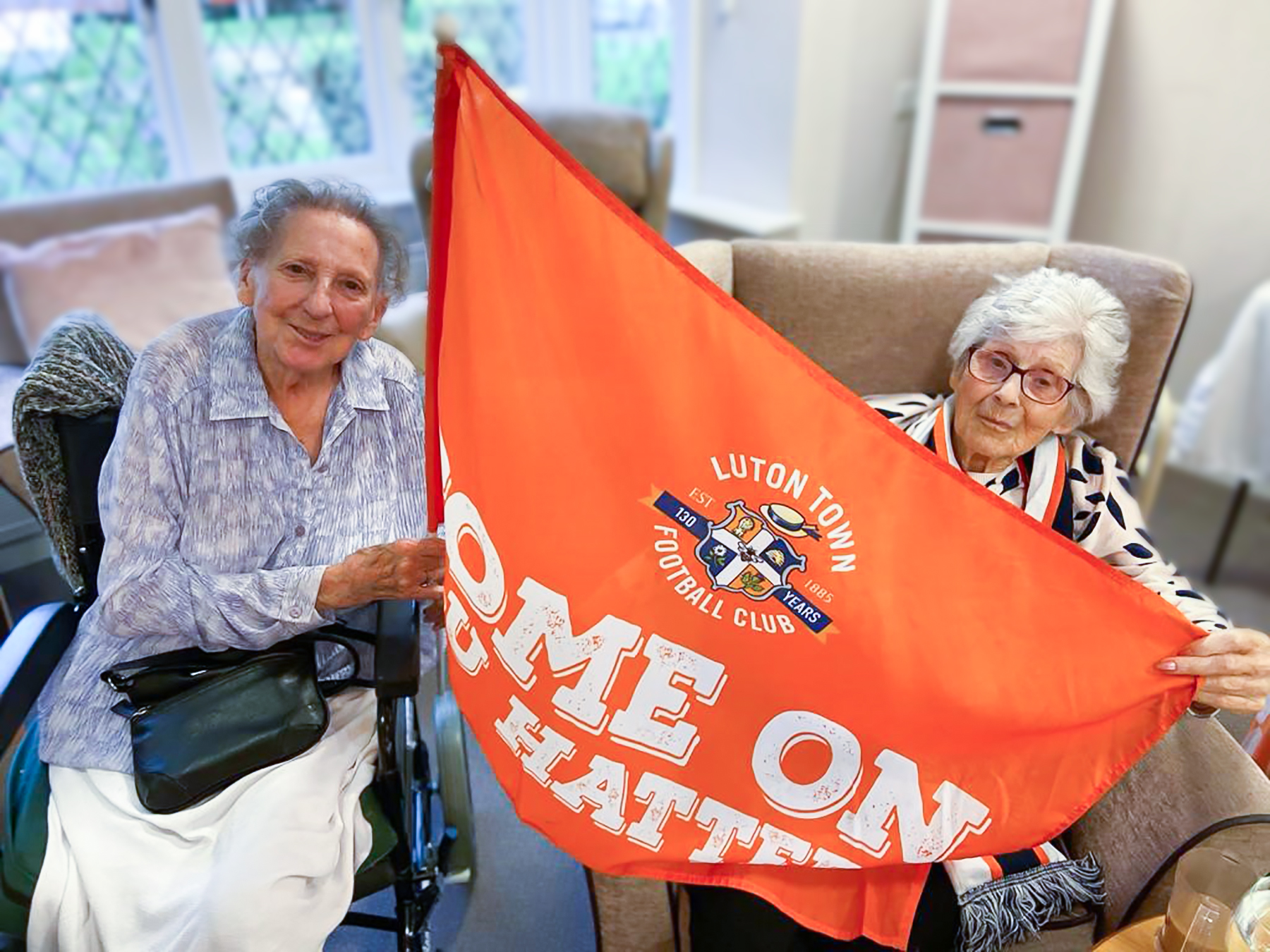 Two residents from Little Bramingham Farm wave a Luton Town Football Club flag