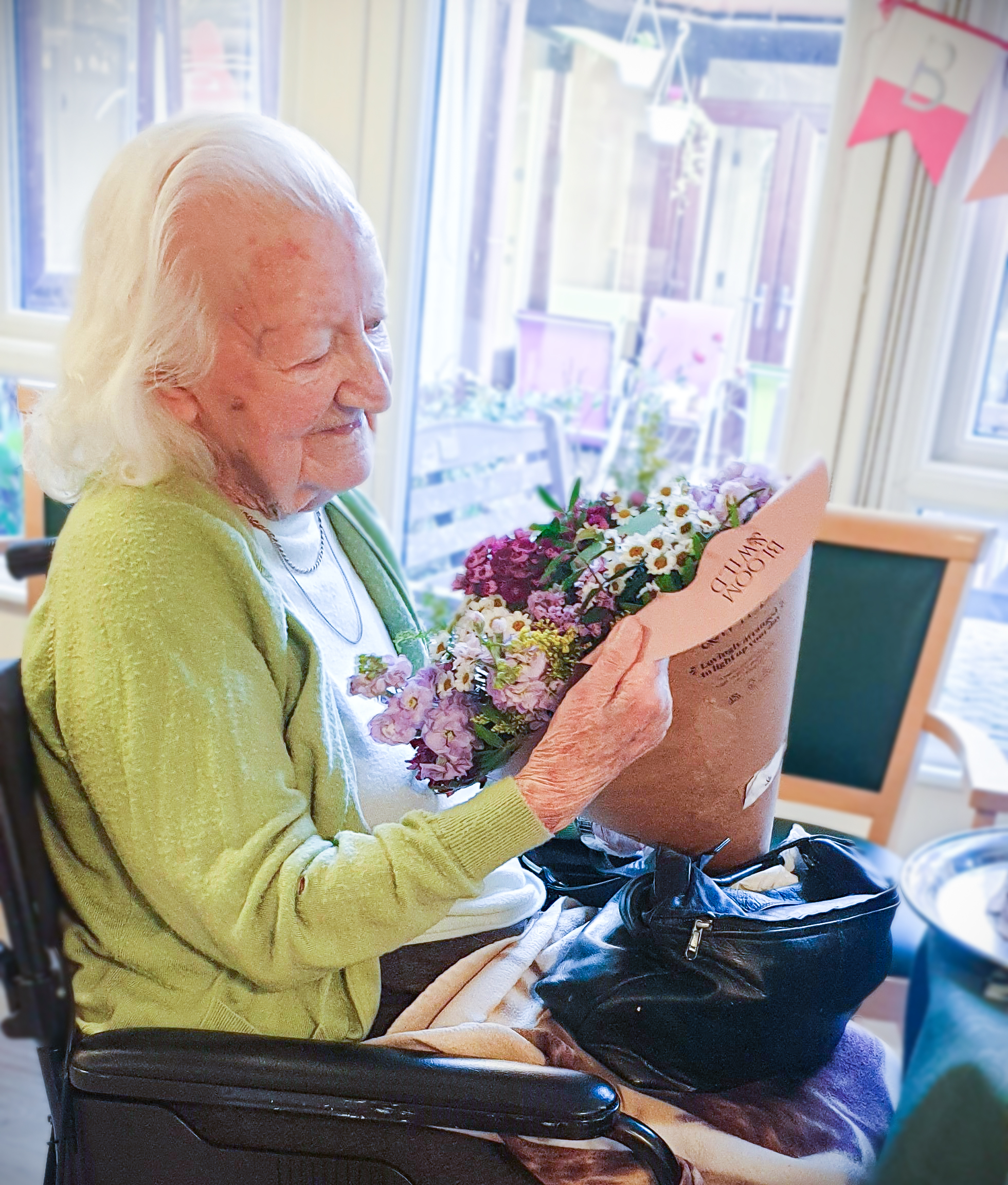 Essex resident Marjorie Wood celebrating her landmark birthday and looking at a bunch of flowers given to her as a gift.