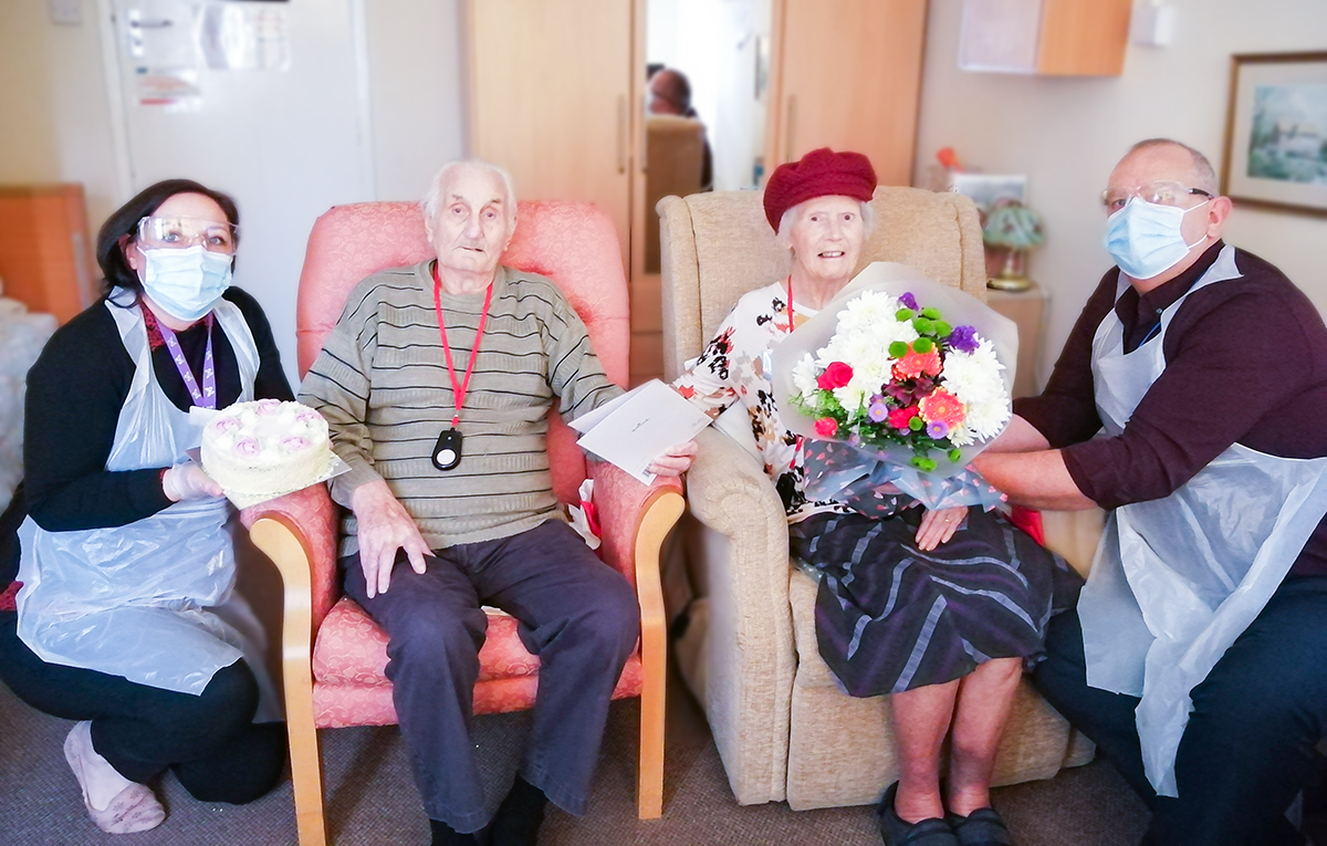 Len and Delia being presented with flowers and a cake on their wedding anniversary