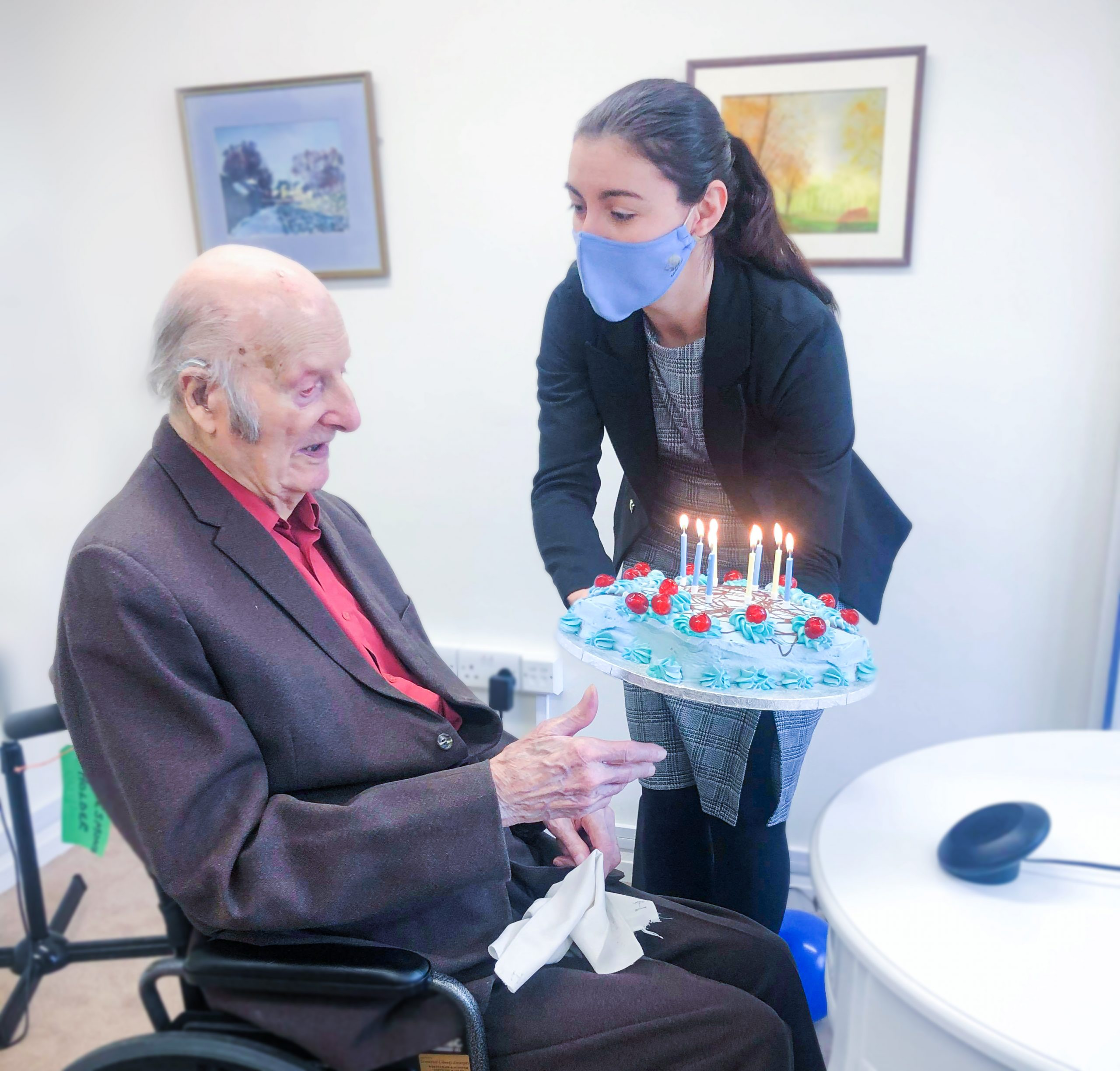Care Home Manager Alina presenting Desmond with his birthday cake