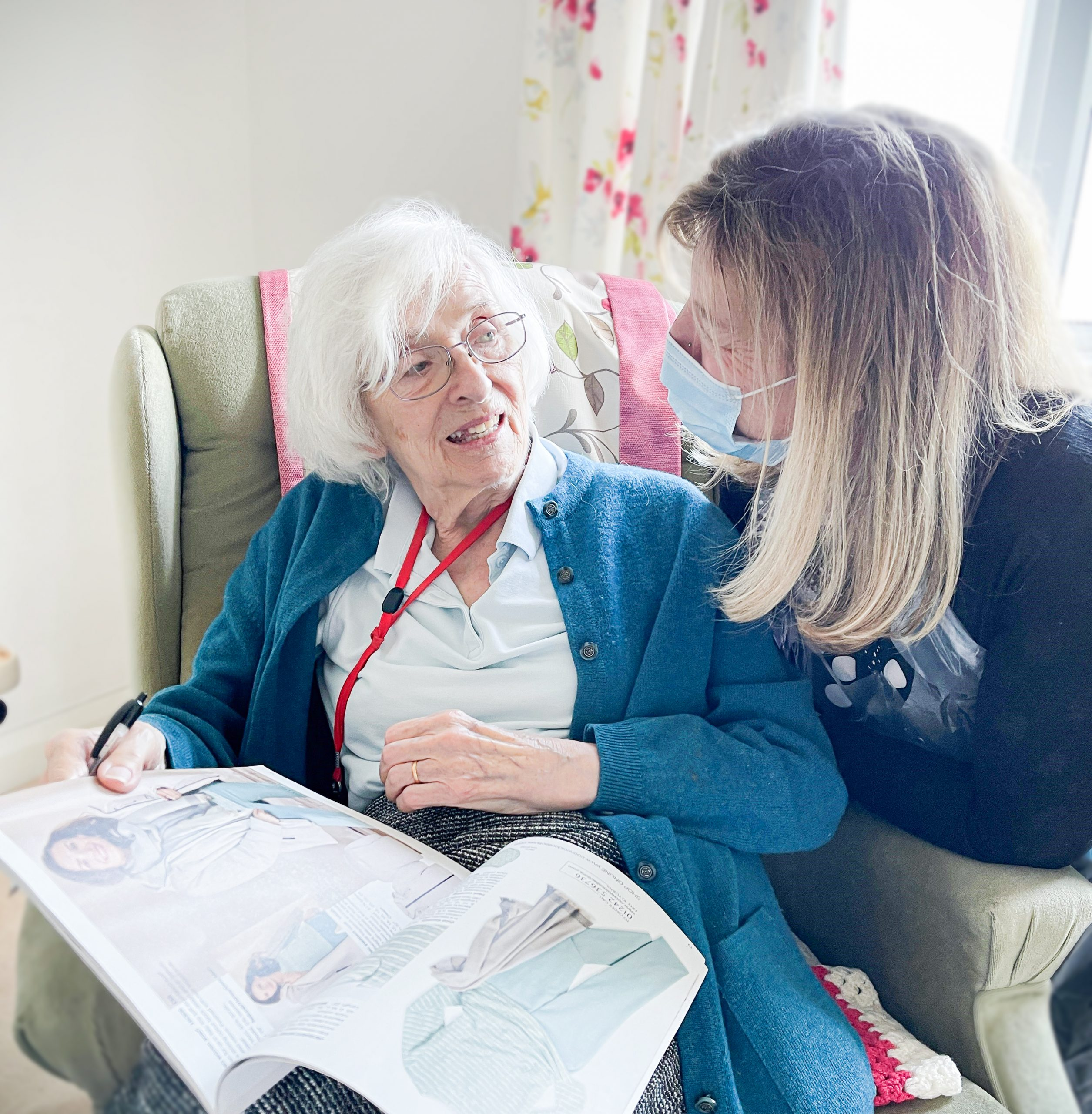 Respite care resident Felicity with Care Home Manager Jan sat together reading a magazine