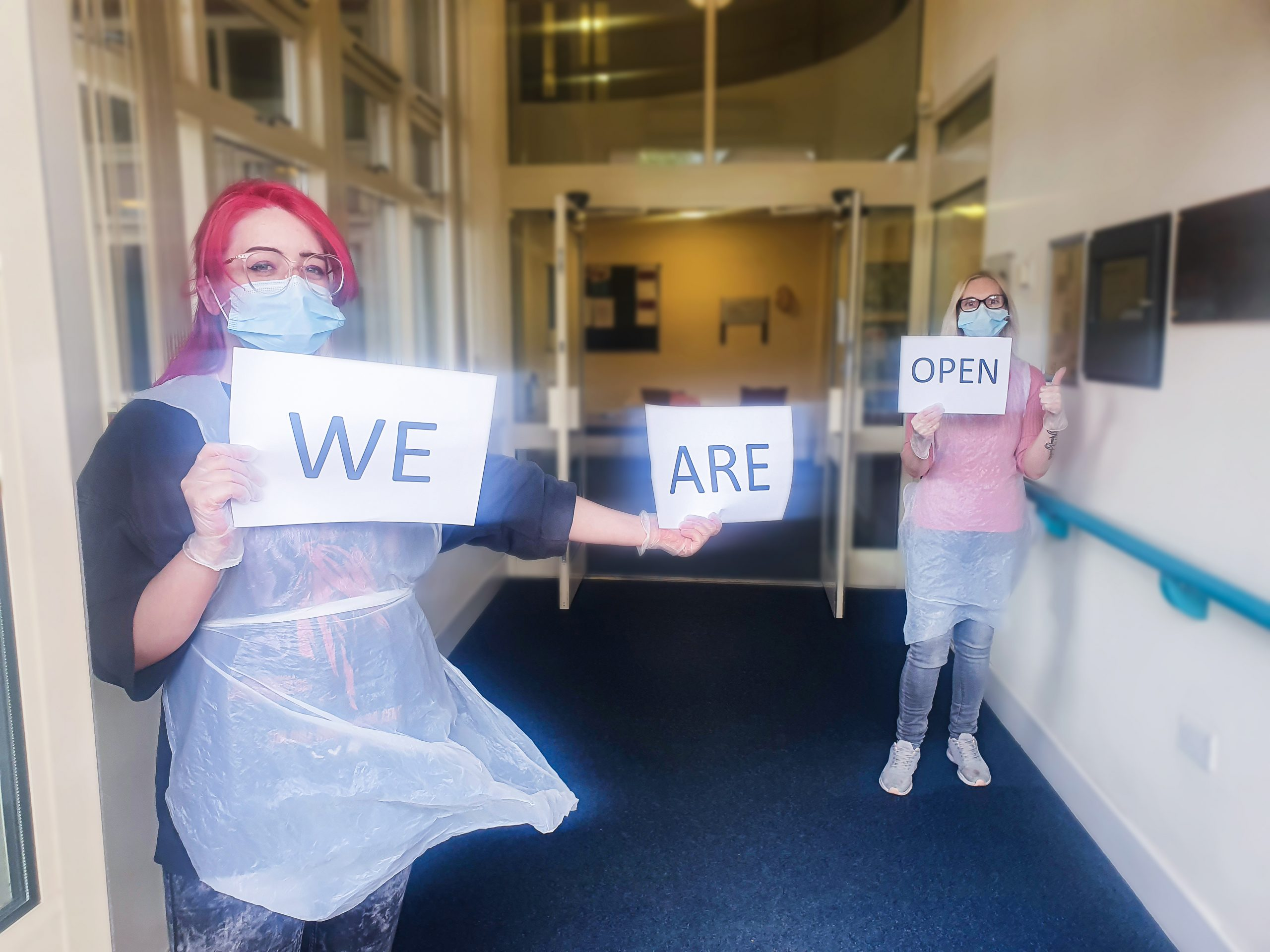 Two Woking Day Care staff members holding a 'We Are Open' sign