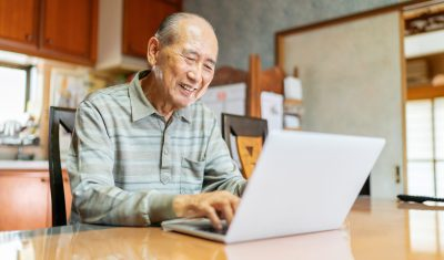 Elderly man using a laptop to stay in touch