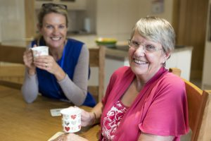 Care worker joins an an elderly woman for a cup of tea while sitting at a kitchen table.