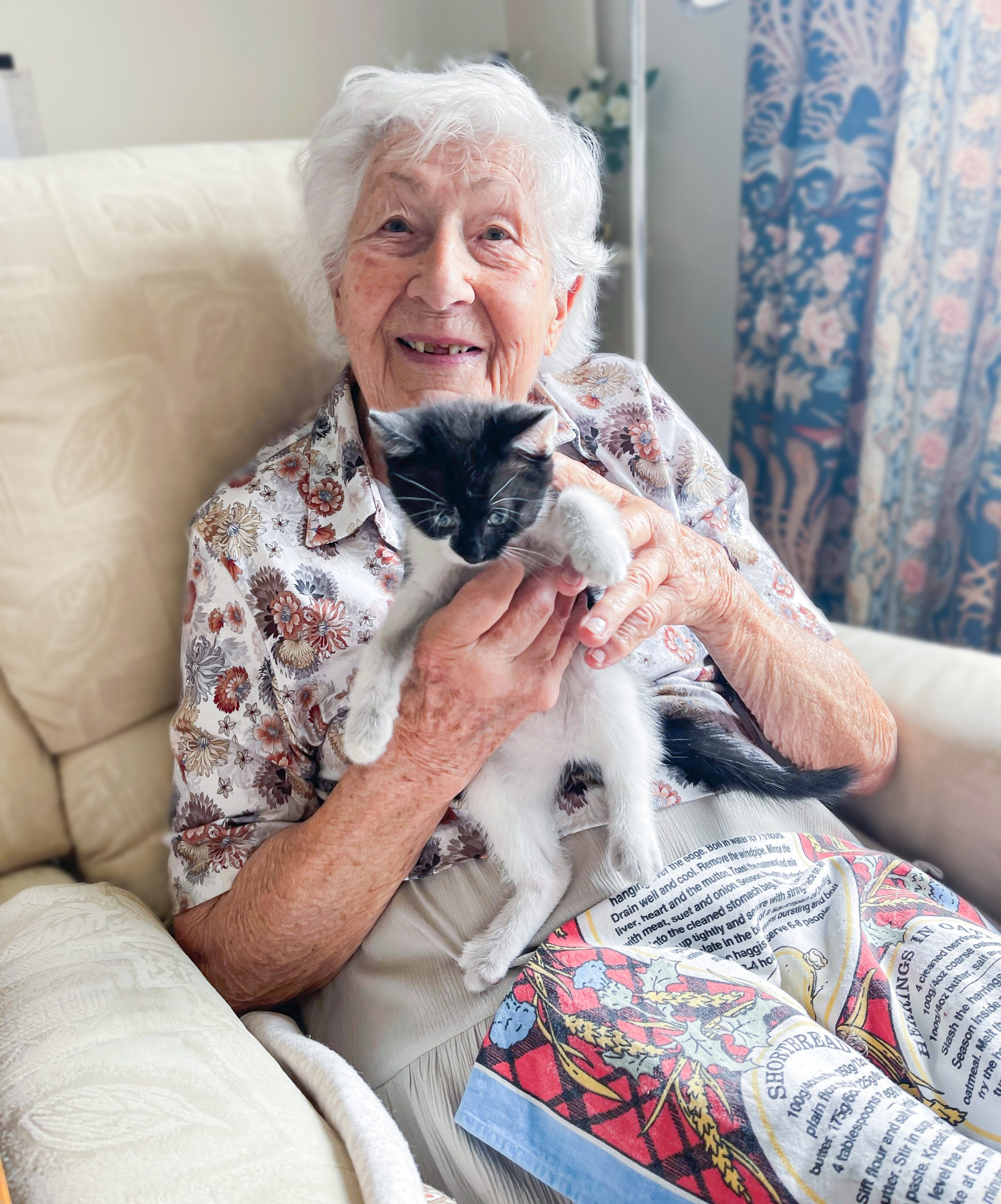 A resident smiling with Slippers the kitten