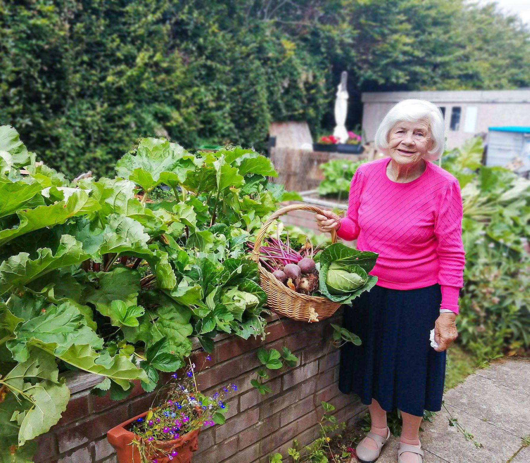 RNNH care home resident holding a basket full of freshly harvested vegetables.