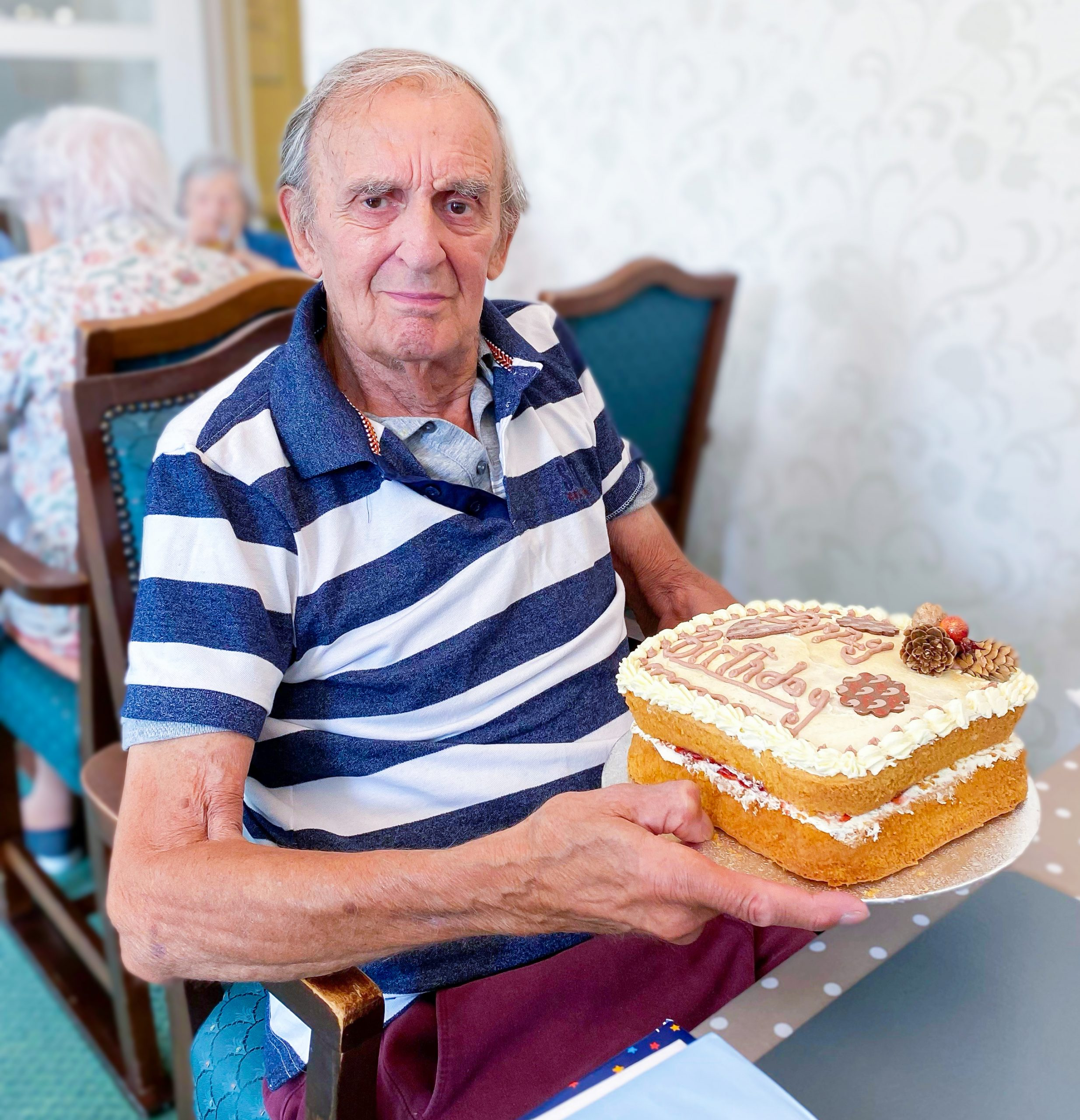 Redcot resident Keith holding a cake on his birthday.