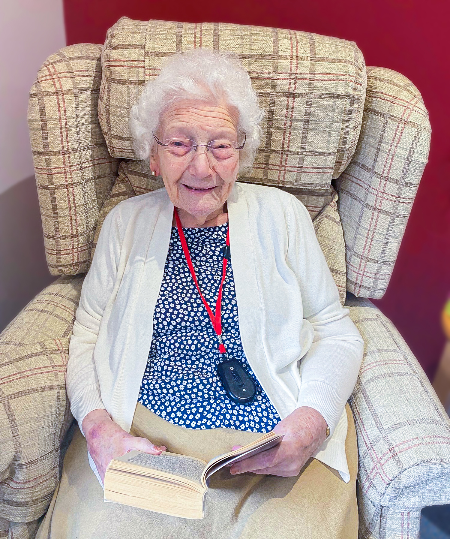 Woking care home resident Sheila sat in her favourite arm chair, smiling at the camera with a book in her hands.