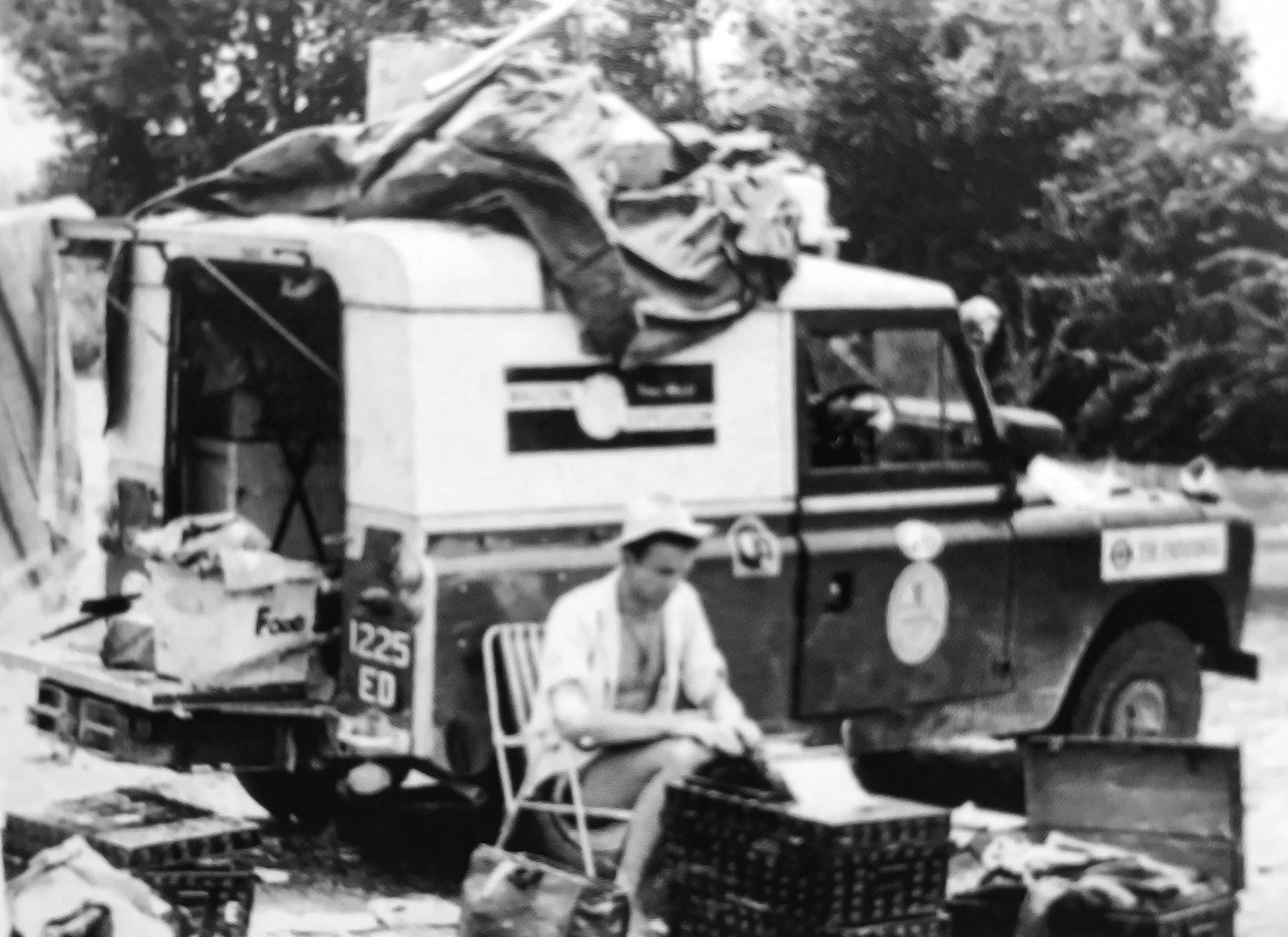A black and white picture of Keith sat by the Land Rover during the trip.